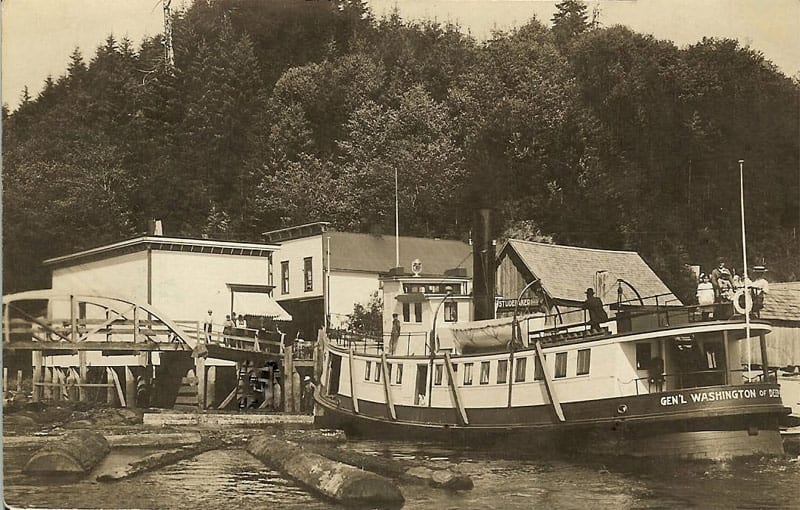 Black and white photo of the 'Gen'l. Washington' docked at Deep River. A group of ladies stand at the stern on the top deck. Two men are also on the top deck (one is leaning on the pilot house). The town of Deep River is visible in the background with four different buildings and storefronts including the Anderson Store along the bank of the river. One of the storefronts has a sign that reads 'Studebaker.'