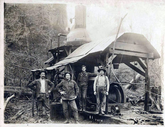 Four loggers in Portland Lumber Company camp posing with a steam donkey